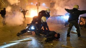 A policeman lays injured on the road after an attack by protesters as his colleagues try to help him during clashes in Athens, Tuesday, March 9, 2021.