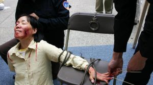 Reenactment of one of the brutal torture methods employed by the CCP officials to coerce female Falun Gong adherents to renounce their faith.