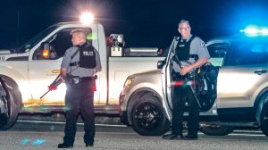 Police officers stand at the scene following a police chase in Carroll County, Ga., on April 12, 2021. (John Spink/Atlanta Journal-Constitution via AP)