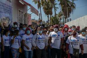 "Migrants wearing ""Biden, please let us in,"" t-shirts at ""El Chaparral"" US border crossing on March 2, 2021."