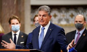 Sen. Joe Manchin (D-W.Va.) removes his mask to speak as bipartisan members of the Senate and House gather to announce a framework for new COVID-19 relief legislation at a news conference on Capitol Hill in Washington on Dec. 1, 2020. (Kevin Lamarque/Reuters)