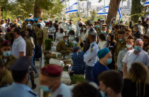 Civilians and soldiers gather by graves of Israeli soldiers during a Memorial Day ceremony for fallen soldiers and victims of attacks, at the military cemetery at Mount Herzl, in Jerusalem, Wednesday, April 14, 2021.