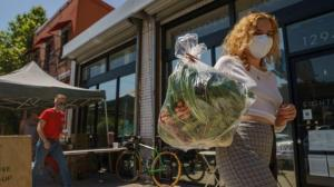 Fashion designer Josie Vand wears a facemask as she retrieves a bag with organic vegetables from a farm box from County Line Harvest in Los Angeles on Friday, April 2, 2021.