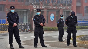 Security personnel gather near the entrance of the Wuhan Institute of Virology during a visit by the World Health Organization team,