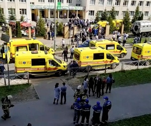 In this image taken from video, an ambulance and police trucks are parked at a school after a shooting, in Kazan, Russia, Tuesday, May 11, 2021. (AP)