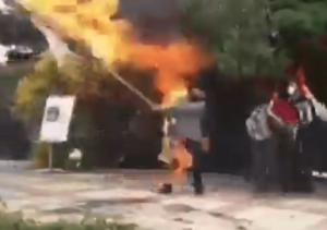 Man caught on fire while burning an Israeli flag. (Twitter screenshot)