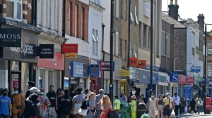 Pedestrians, some wearing face coverings due to Covid-19, walk past shops in Hounslow,