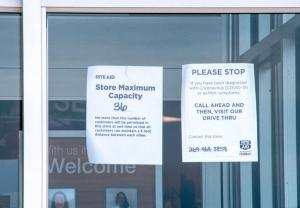 A Rite Aid store in Coloma, Mich., posts a sign of COVID-19 capacity restrictions on April 23, 2020.