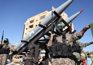 Members of the Ezz-Al Din Al-Qassam Brigades, the armed wing of the Hamas movement, parade on trucks with rockets in a street in Khan Yunis, in the southern Gaza Strip,