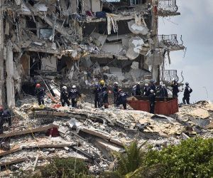 Members of the South Florida Urban Search and Rescue team look for possible survivors in the partially collapsed 12-story Champlain Towers,