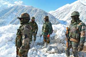 Indian army soldiers stand on a snow-covered road near Zojila mountain pass, bordering China. (TAUSEEF MUSTAFA/AFP via Getty Images/TNS)