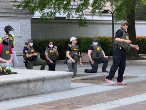 Large group of FBI agents (25) take a knee with protestors near the national archive.