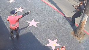 A suspect is seen pointing an object toward a police officer along the Hollywood Walk of Fame, July 15, 2021. (Los Angeles Police Department)