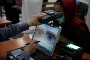 An employee scans the eyes of a woman for biometric data needed to apply for a passport, at the passport office in Kabul, Afghanistan, on June 30, 2021. | Rahmat Gul/AP Photo