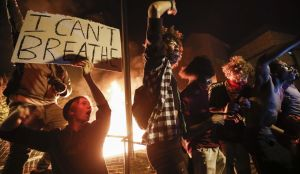 In this May 28, 2020, protesters demonstrate outside of a burning Minneapolis 3rd Police Precinct in Minneapolis. (AP Photo/John Minchillo, File)