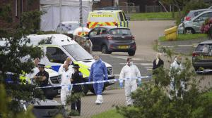 Forensic officers walk in Biddick Drive in the Keyham area of Plymouth, England on Friday, where six people were killed in a shooting incident. (Ben Birchall/PA via AP)