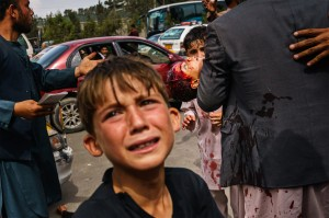 A man carries a bloodied child, as a woman lays wounded on the street after Taliban fighters use guns fire, whips, sticks and sharp objects to maintain crowd control over thousands of Afghans who continue to wait outside the Kabul Airport. MARCUS YAM / LOS ANGELES TIMES via Getty Images