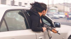 A photo out of San Francisco shows a woman leaning out of a moving car while holding an AK47.  (San Francisco Police Department/Twitter)