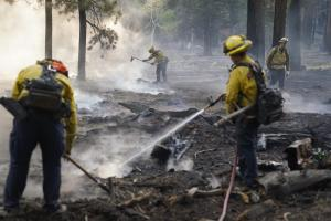 Firefighters put out hot spots near South Lake Tahoe, Calif., Wednesday, Sept. 1, 2021. Authorities are reporting progress in the battle to save communities on the south end of Lake Tahoe from a huge forest fire. (AP Photo/Jae C. Hong)