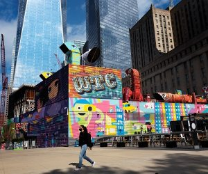 A woman walks by the colorful murals that surround the foundation for 2 World Trade Center, Wednesday, Sept. 8, 2021 in New York. (Mark Lennihan/AP)