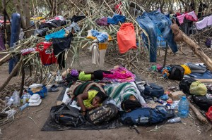 Haitian immigrants lie in their makeshift dwelling constructed of tree branches and carrizo cane. John Moore/Getty Images