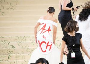 Rep. Alexandria Ocasio-Cortez (D-NY), appears at the 2021 Met Gala maskless in her highly fashionable and subversive gown, as masked workers and servants surround her, ensuring her safety and a smoothly running party, on September 13, 2021 in New York City. (Photo by Noam Galai/GC Images)
