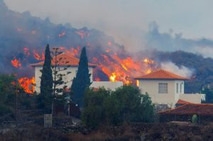 Lava flows behind a house following the eruption of a volcano in the Cumbre Vieja national park at Los Llanos de Aridane, on the Canary Island of La Palma, September 20, 2021. REUTERS/Borja Suarez