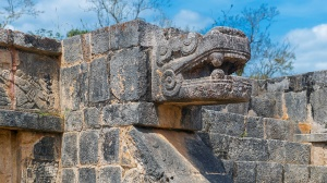 Stone sculpture of the feathered snake and god Quetzalcoatl, deity of creation and life for Aztec and Maya civilization, Chichen Itza, Mexico.