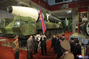 North Korean leader Kim Jong Un speaks in front of what the North says is an intercontinental ballistic missile displayed at an exhibition of weapons systems in Pyongyang, North Korea.