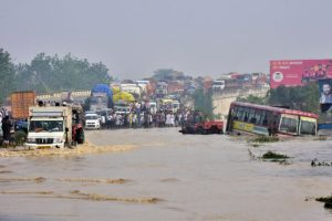 Commuters stand on a flyover on a flooded national highway after river Kosi overflowed following heavy rains near Rampur in India's Uttar Pradesh state on Oct. 20, 2021. (AFP via Getty Images)